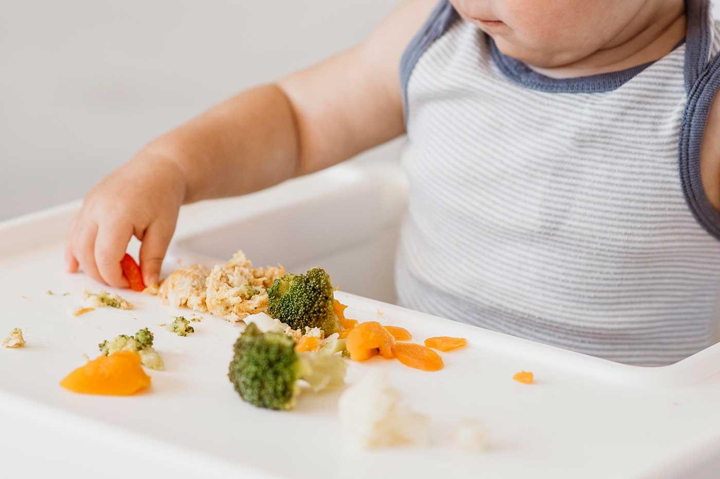 cute-baby-boy-highchair-choosing-what-eat-1400