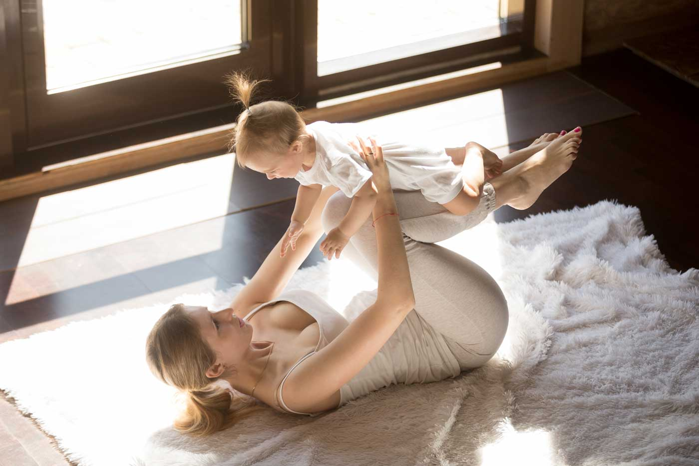 young-smiling-yogi-mother-baby-daughter-exercising-home-1400